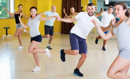 Happy men and women enjoying active dance Banque d'images