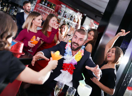 Guy on corporate party in Hawaiian style in bar Imagens