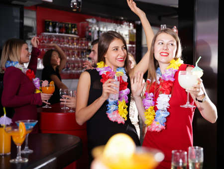 Female colleagues on company party in Hawaiian style in bar Imagens