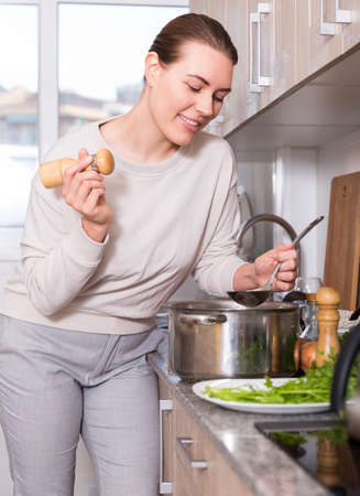 Housewife is cooking soup in pot and salt it in the kitchen Reklamní fotografie