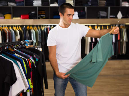Nice man chooses clothes in a sports shop