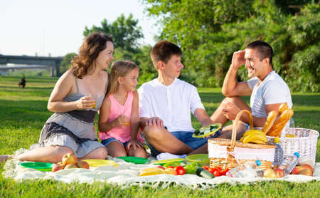 Happy parents with two kids having picnic together on green meadow in park