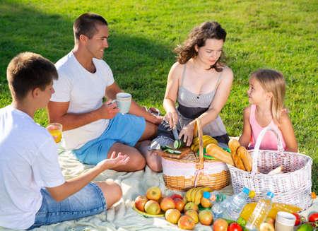 Woman with husband and children enjoying picnic