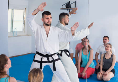 Beardy young instructor is showing new martial moves to adults