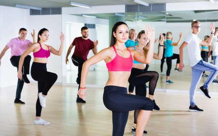 Men women performing modern dance in fitness studio