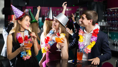 Portrait of joyous women and men in caps with cocktails