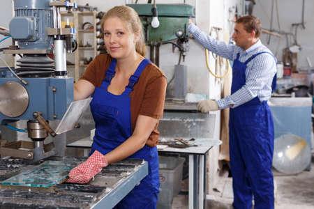 Female glazier working with glass drilling machine