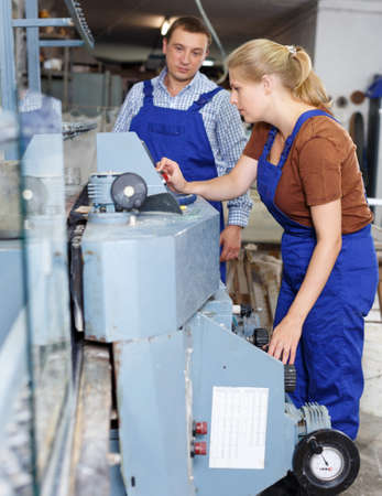 Woman with male assistant working on glass beveling machine Stock fotó