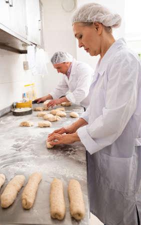 Female baker shaping dough