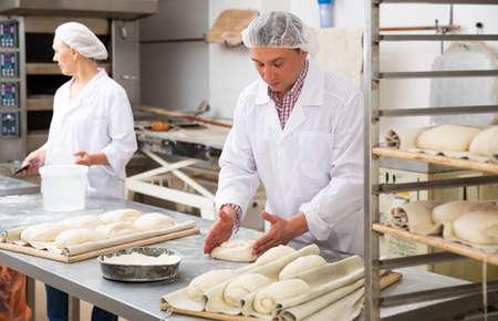 Baker forming dough for baking bread