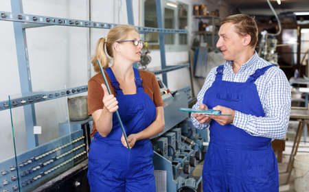 Young woman and her male colleague busy working Stock fotó