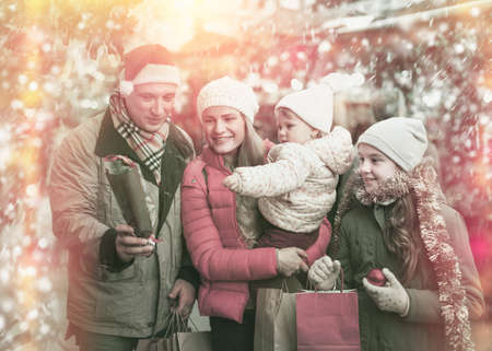 Parents with daughters choosing Christmas toys Standard-Bild