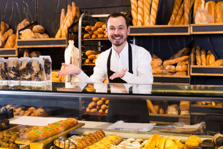 Young male seller showing assortment of bakery Foto de archivo