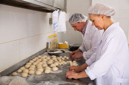Two bakers portioning and shaping dough