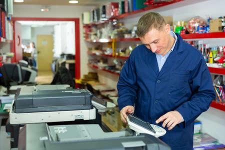 Service engineer using a copy machine Stock Photo