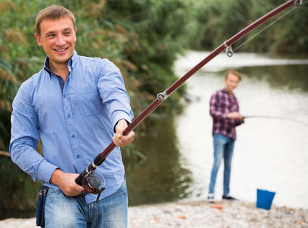 man casting line for fishing on river .