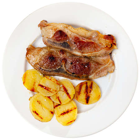 Appetizing fried pork with potatoes and herbs
