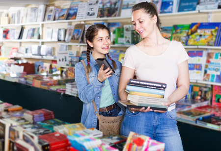 Nice girl picking textbooks with telephone
