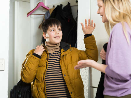 Young woman and son in jacket chatting near door indoors