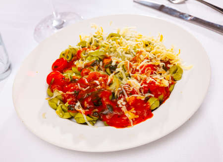 Green tortellini with baked red sweet pepper in tomato sauce
