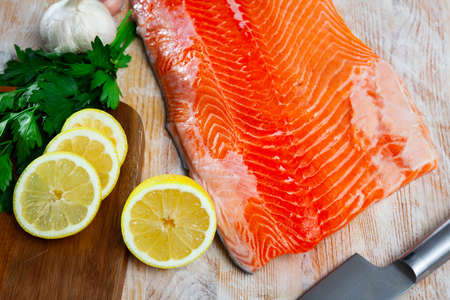 Salmon fillet on cutting board with lemon and parsley Stock Photo