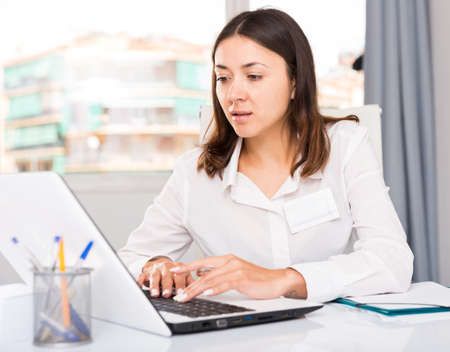Young woman working with laptop and papers at the office