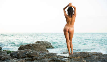 Back view of woman standing on stones at ocean shore