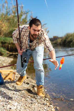 Adult man standing near river and pulling fish expressing emotions of dedication