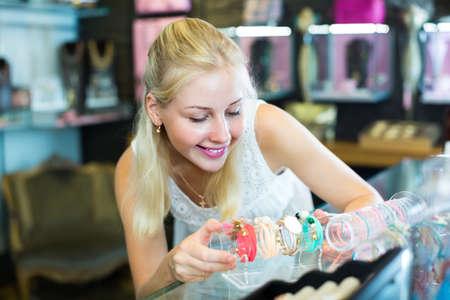 girl choosing bracelet in bijouterie shop.