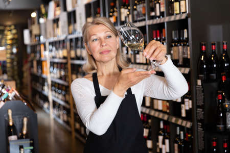Woman wine producer inspecting quality of wine