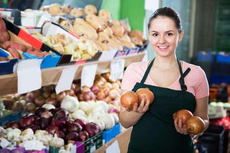 Saleswoman offering onions