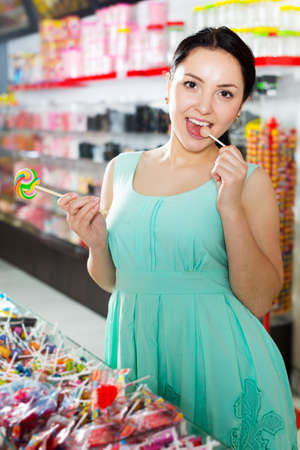 Woman posing to photographer with lollypop