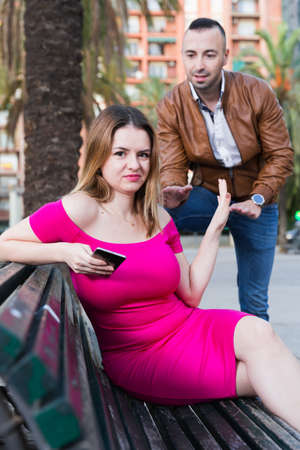 Girl is sitting with phone and inaccessibility for stranger man