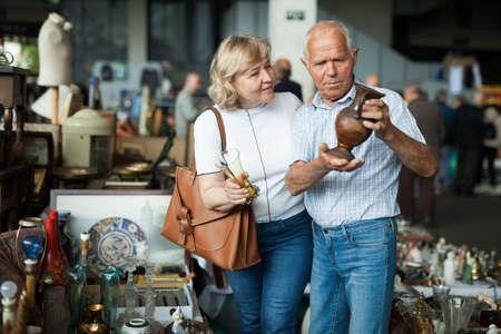 Elderly family choose handmade vase at flea market
