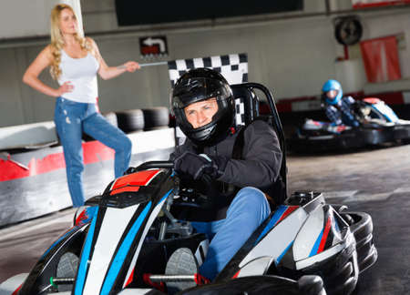Man in helmet driving car for karting in sport club, woman with flag on background Stockfoto
