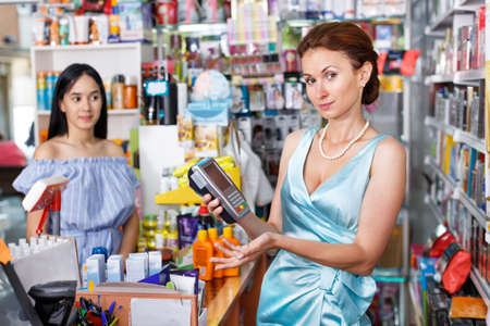 Saleswoman helping to client with payments in salon