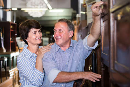 Smiling adult woman with her husband are buying antique cupboard in store