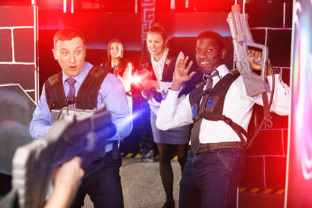 Group of colleagues holding laser pistols playing laser tag game