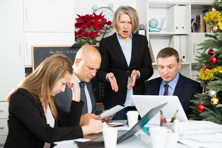 Angry business woman berating his managers pointing out shortcomings