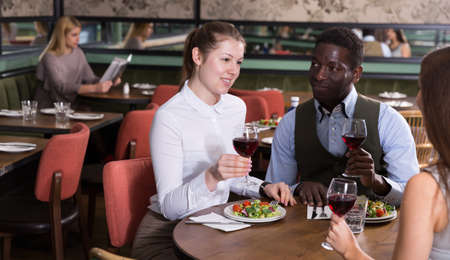 Cheerful pair with female friend at restaurant