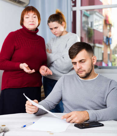 Upset guy with documents and dissatisfied family behind