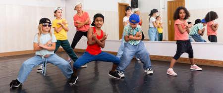 Preteen girls and boys hip hop dancers doing dance workout