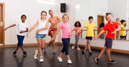 Tweens dancing with coach in choreography class Imagens
