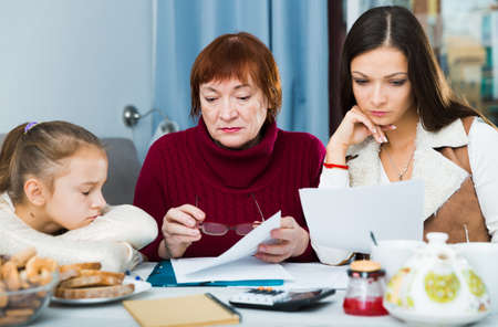 Family faced financials troubless, sitting with bills Фото со стока