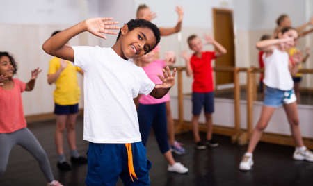 Afro boy showing dance elements at class