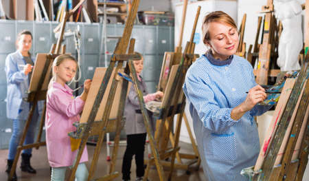 Students working patiently during painting class at art studio