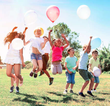 Happy children holding ballons and jumping together in park