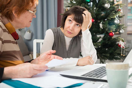 Upset woman and her mother with papers