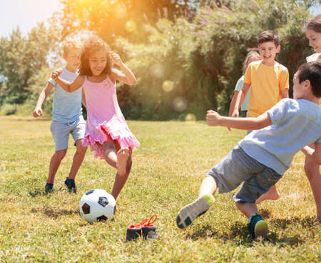 Group of happy schoolchildren playing football together