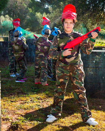 Boy paintball player in camouflage standing with gun before playing outdoors Imagens